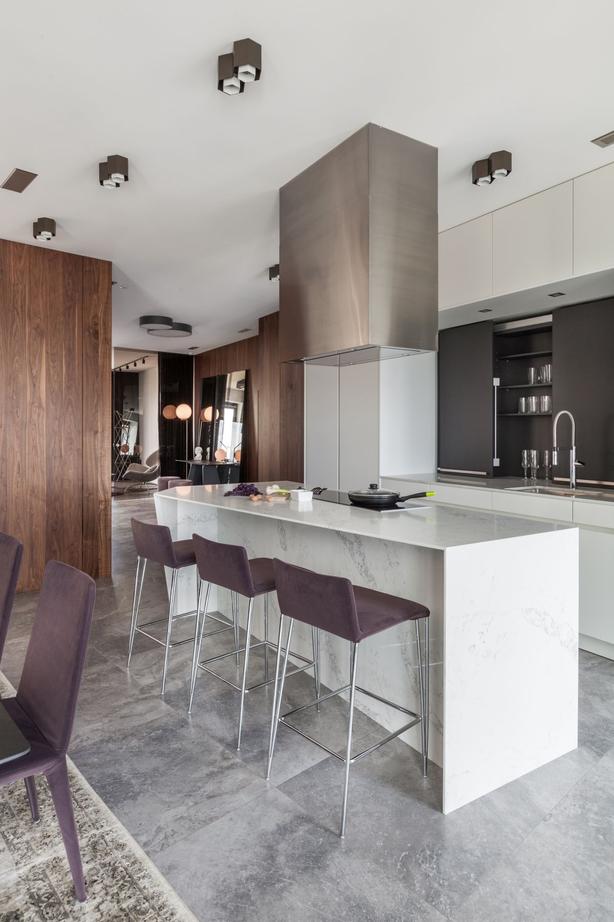 The kitchen island doubles as a bar and the stools match the dining chairs creating a smooth transition