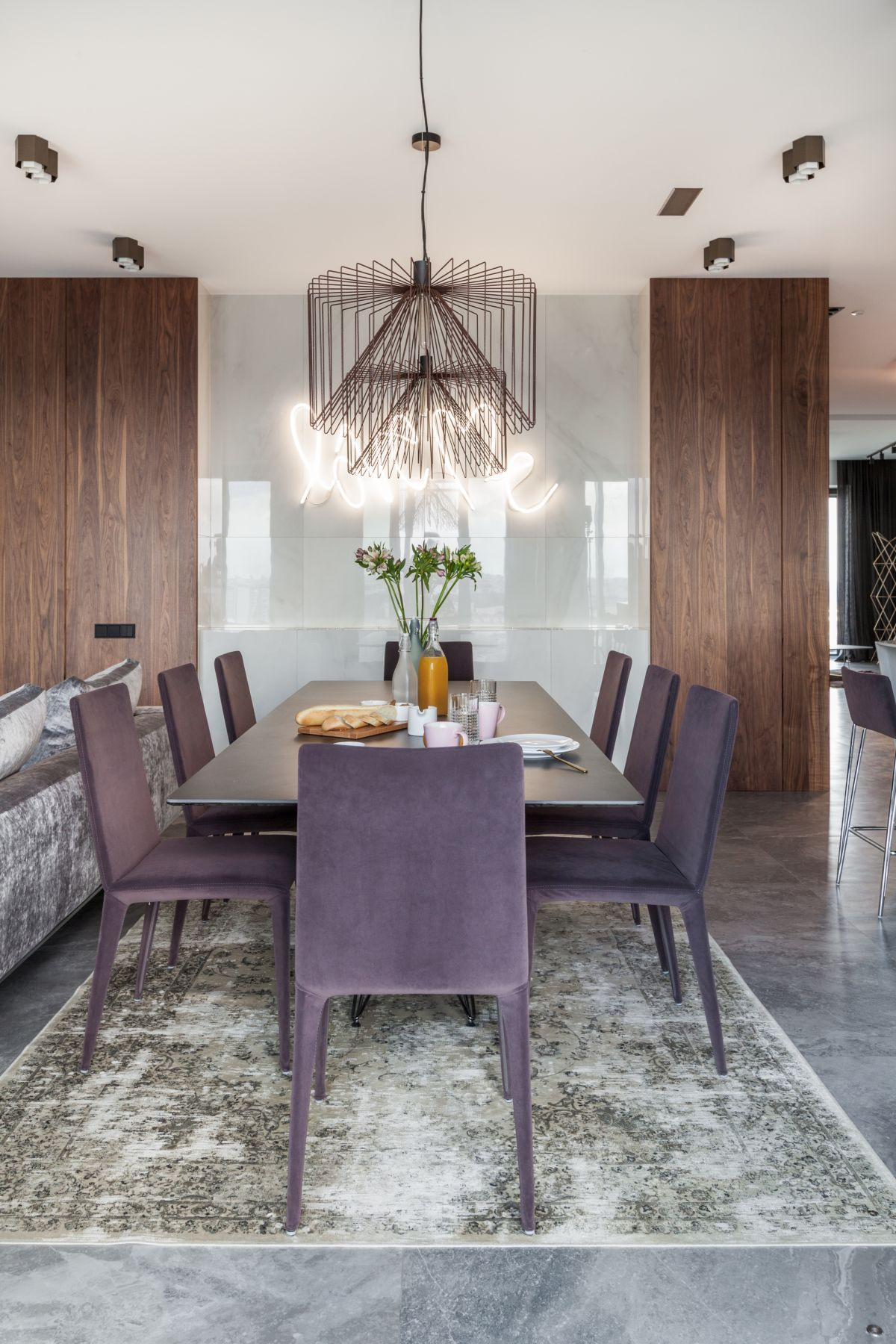 The dining area is framed by a soft and velvety area rug and features beautiful purple chairs