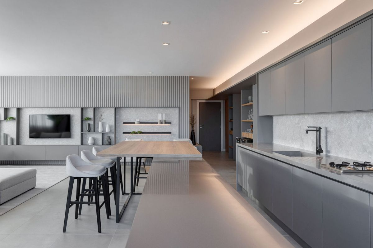 The kitchen has a large island with a bar extension that transitions into the living room