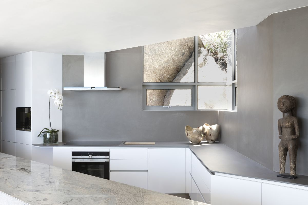 The kitchen has an unusual layout and a minimalist design centered around whites and grays