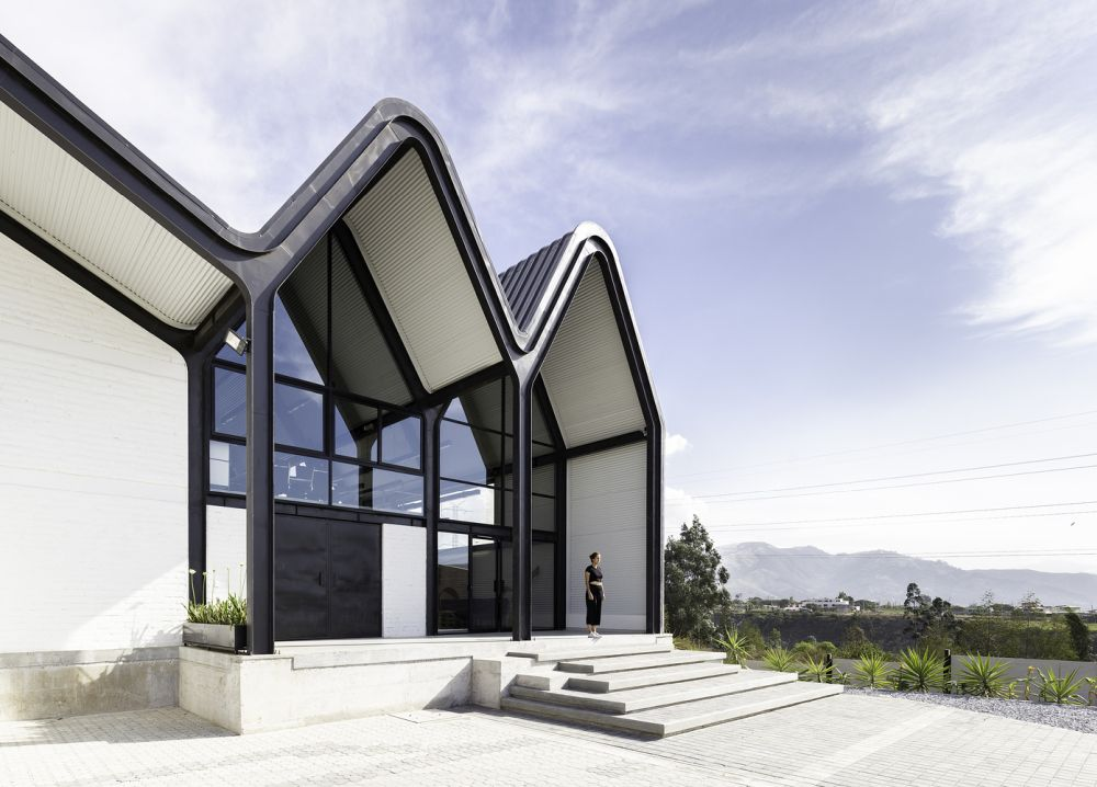 The undulating gable roofs mimic the mountain range in the distance