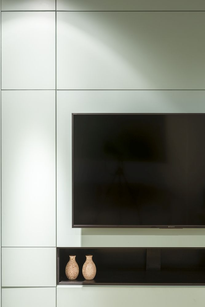 The TV is mounted onto the cabinet and features a small niche underneath it