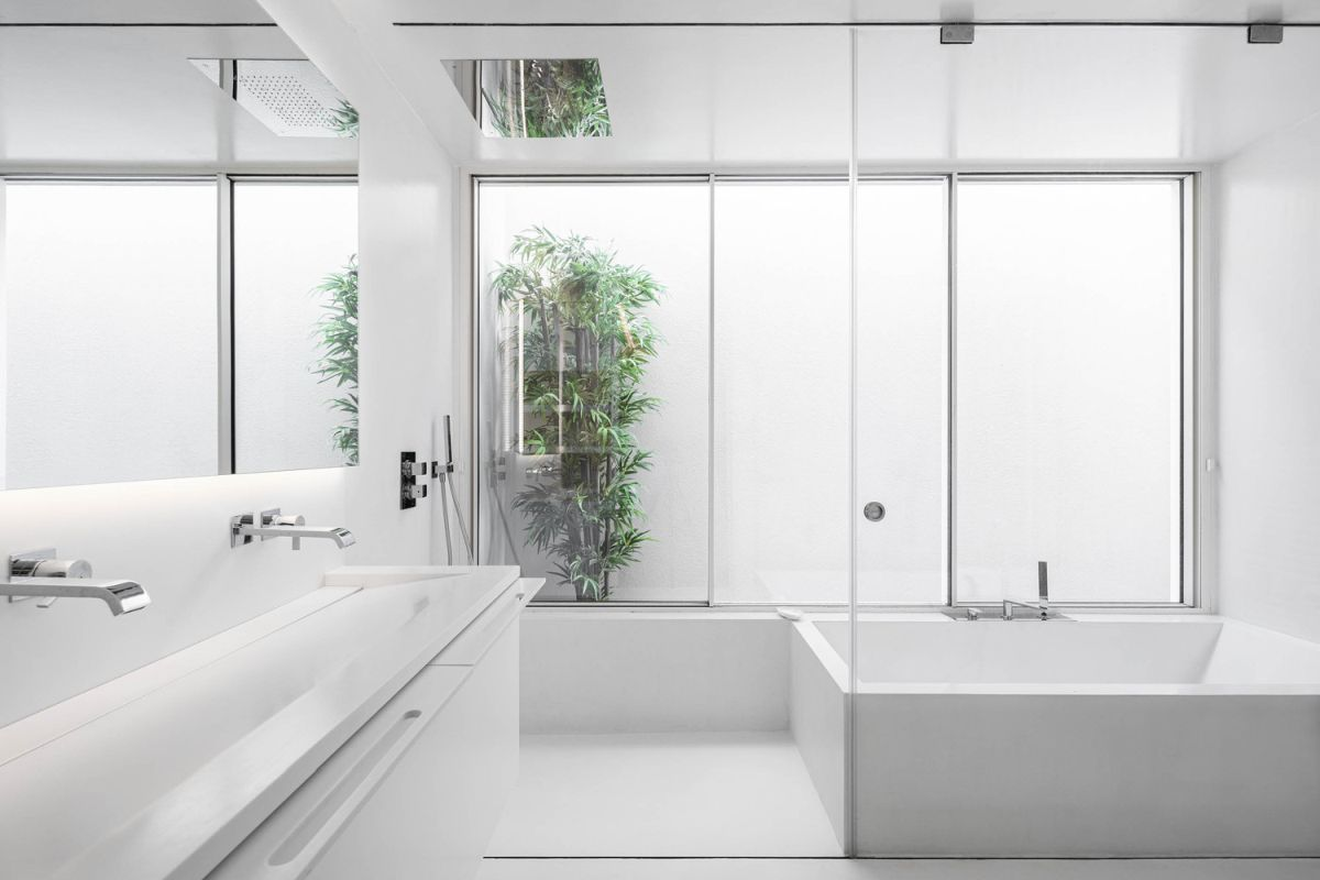 Similarly, a white decor combined with glass surfaces and large mirrors give this bathroom a very fresh look