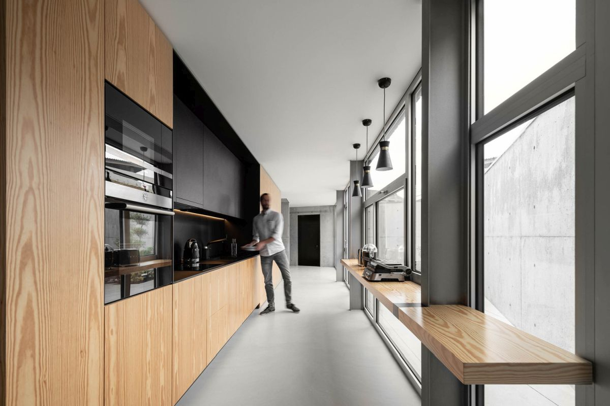 The kitchen is long and narrow and has a floating bar surface along the glass wall