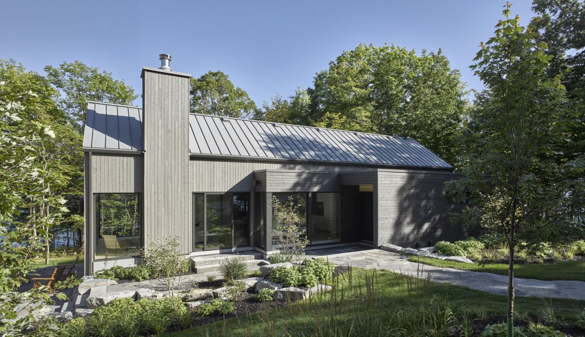 The light grey exterior and gabled roof give the house a modest appearance reminiscent of the old cottages