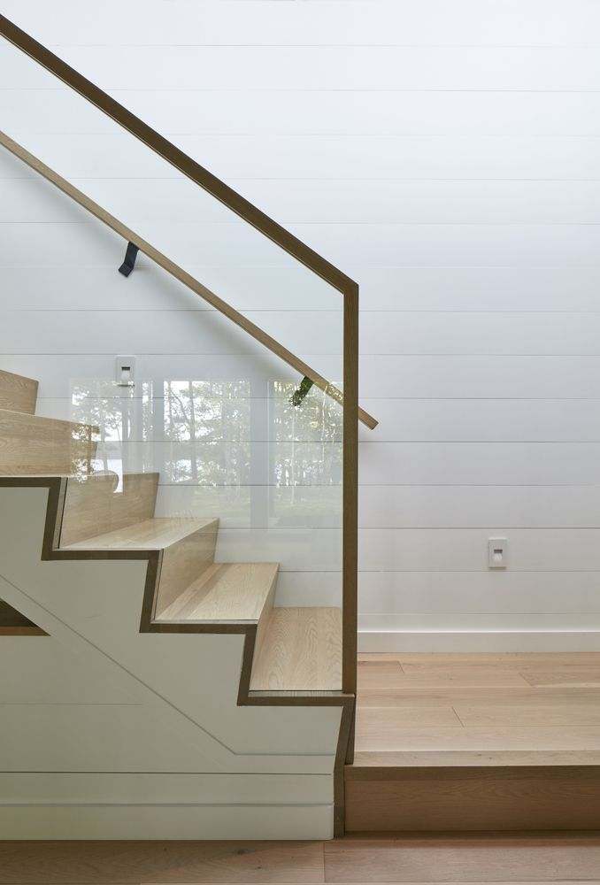 A wooden staircase with glass guardrails connects the spaces on a vertical axis