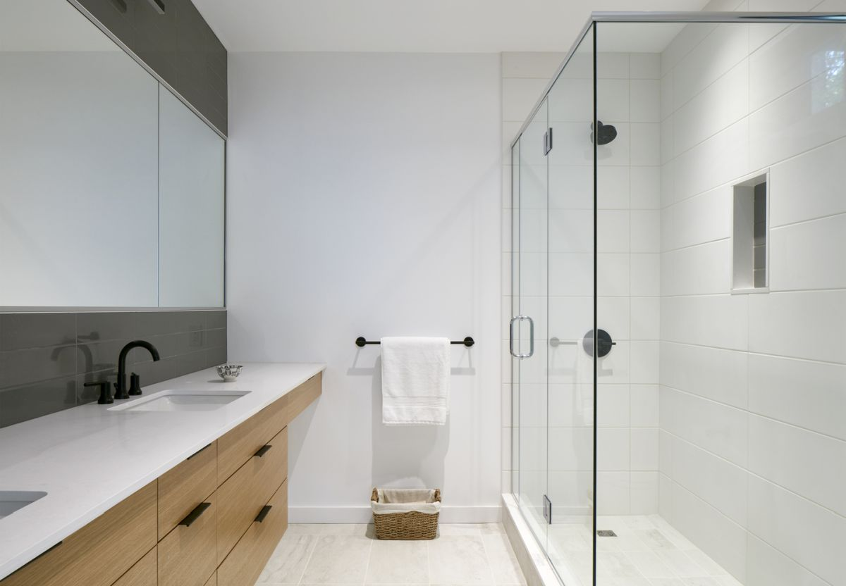 A glass walk-in shower occupies a large section of the bathroom but doesn't make it feel cluttered