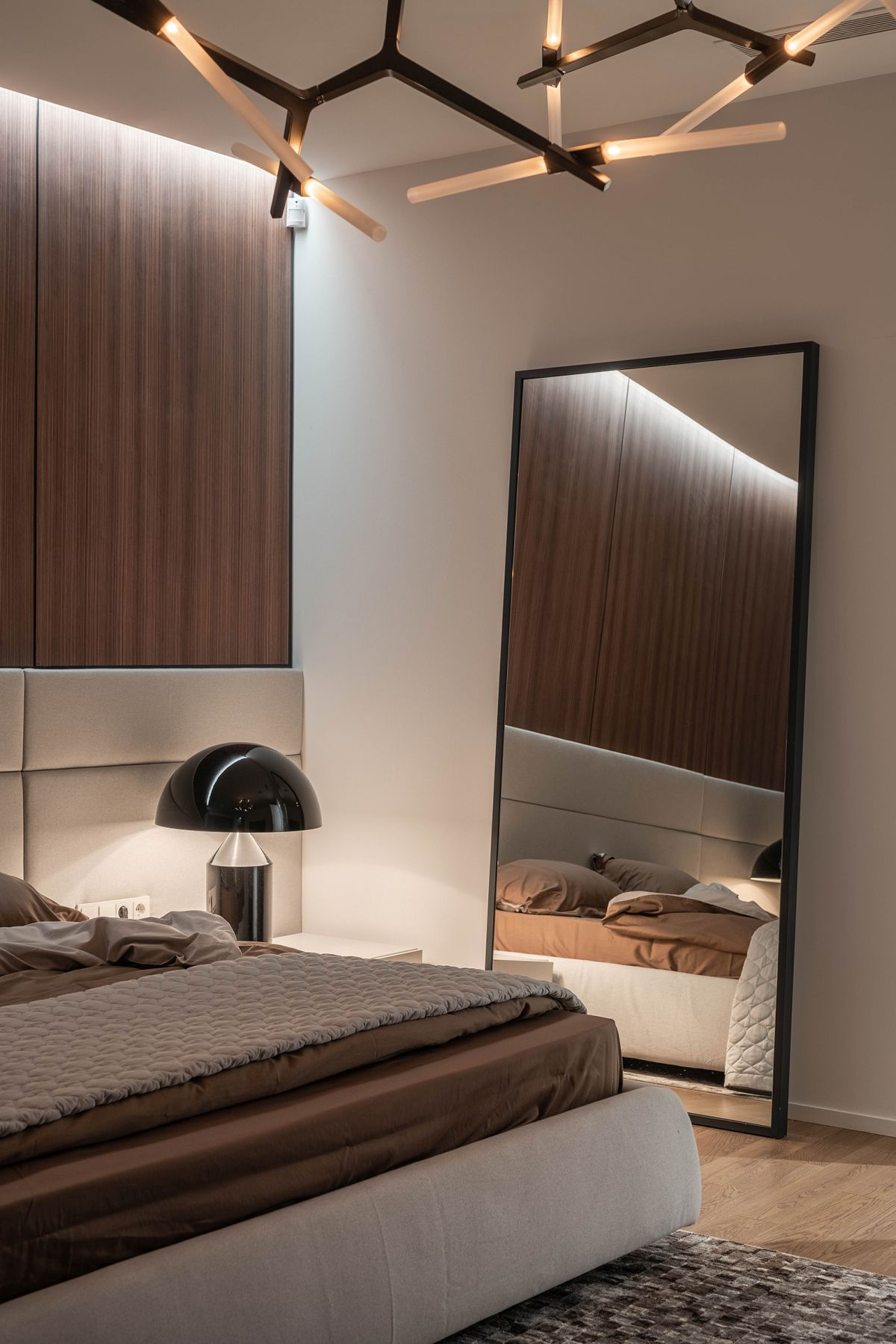 A large mirror casually leans against the wall, adding depth and elegant to this bedroom