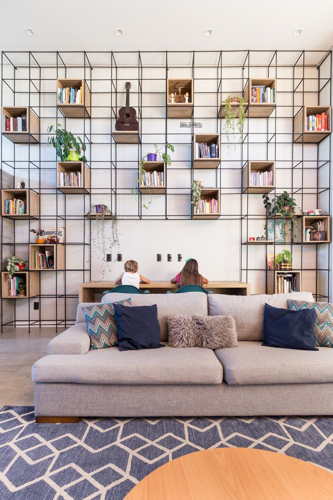 A large multipurpose bookcase covers a big wall section in the living room, featuring wooden cubbies