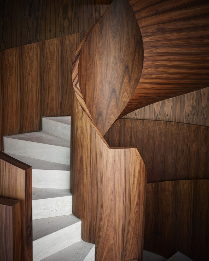 The wood's beautiful coloring and natural patterns contrast with the light grey stairs