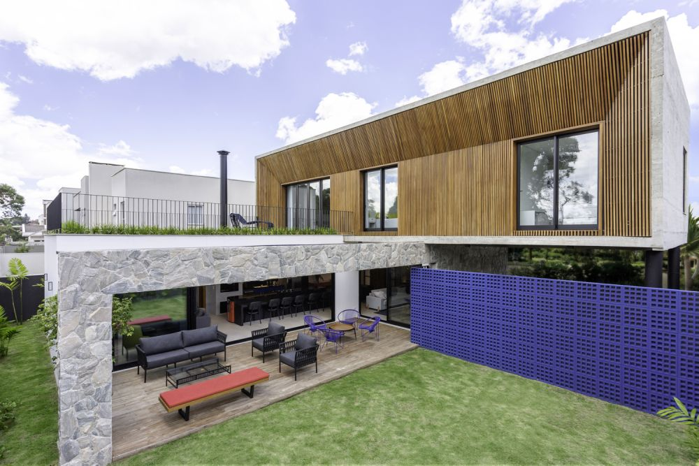 The rear section of the house opens onto a stone and wood deck and a generous garden