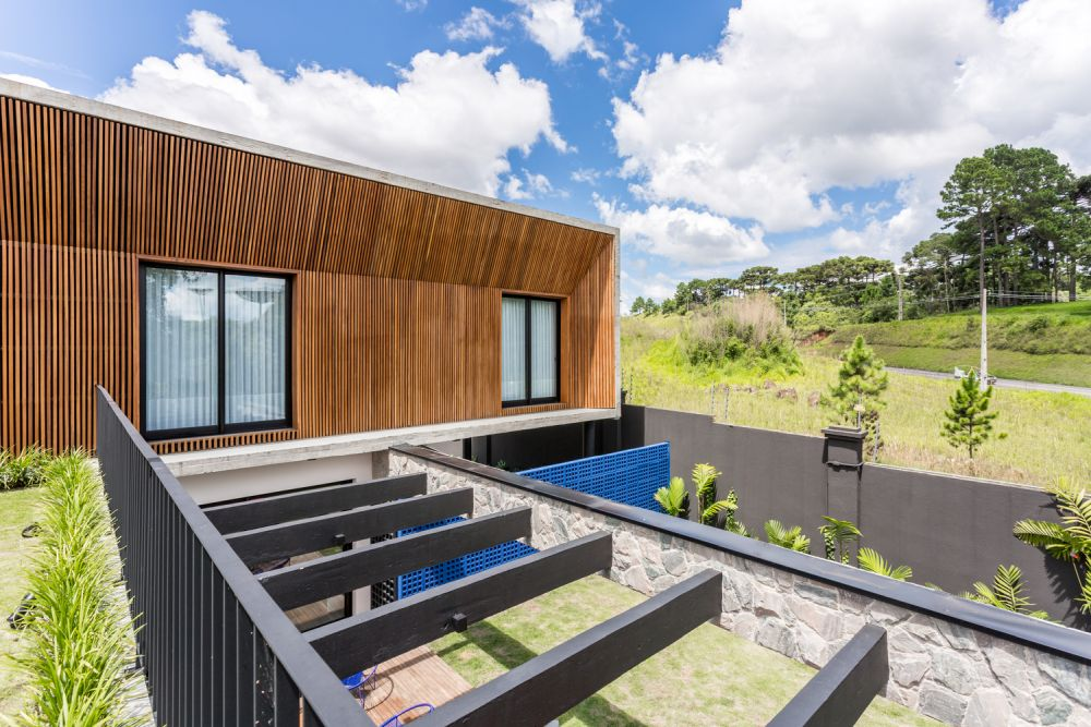 The garden-facing upper volume is also covered in thin wooden slats and match the front door area