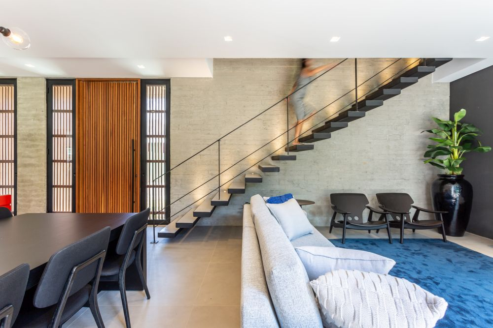 The floating staircase which connects the two floors has a very sleek and unobtrusive design