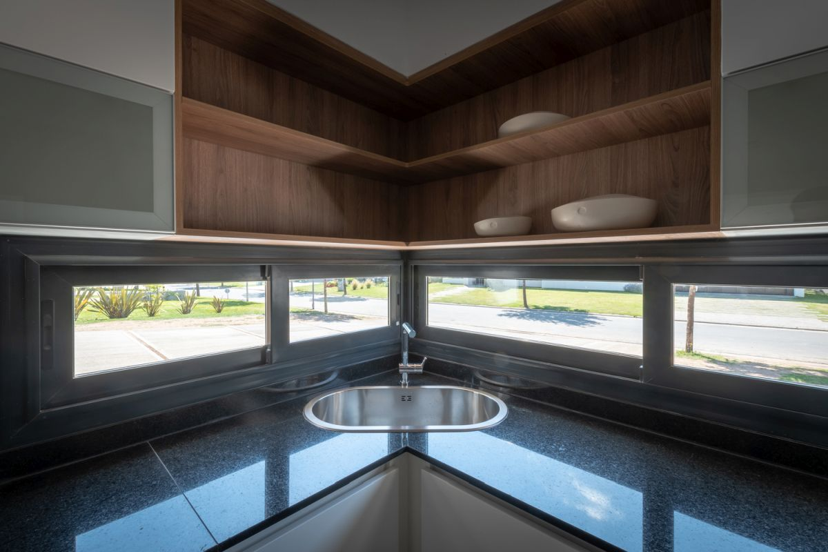 The kitchen sink is positioned in the corner where it takes advantage of the natural light coming through the windows