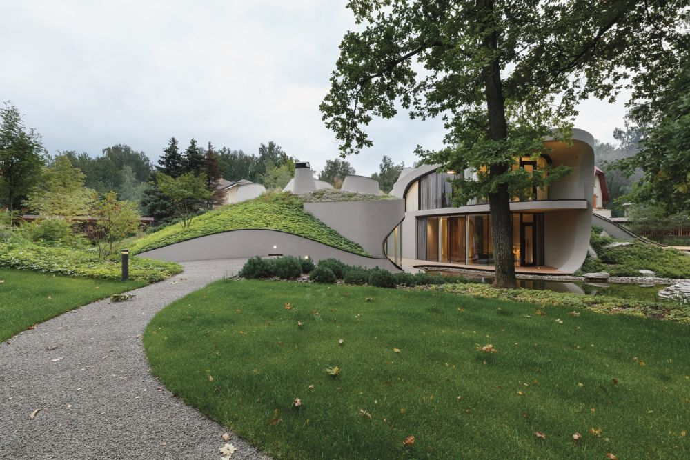 The green roof of the house undulates and seamlessly transitions into the garden