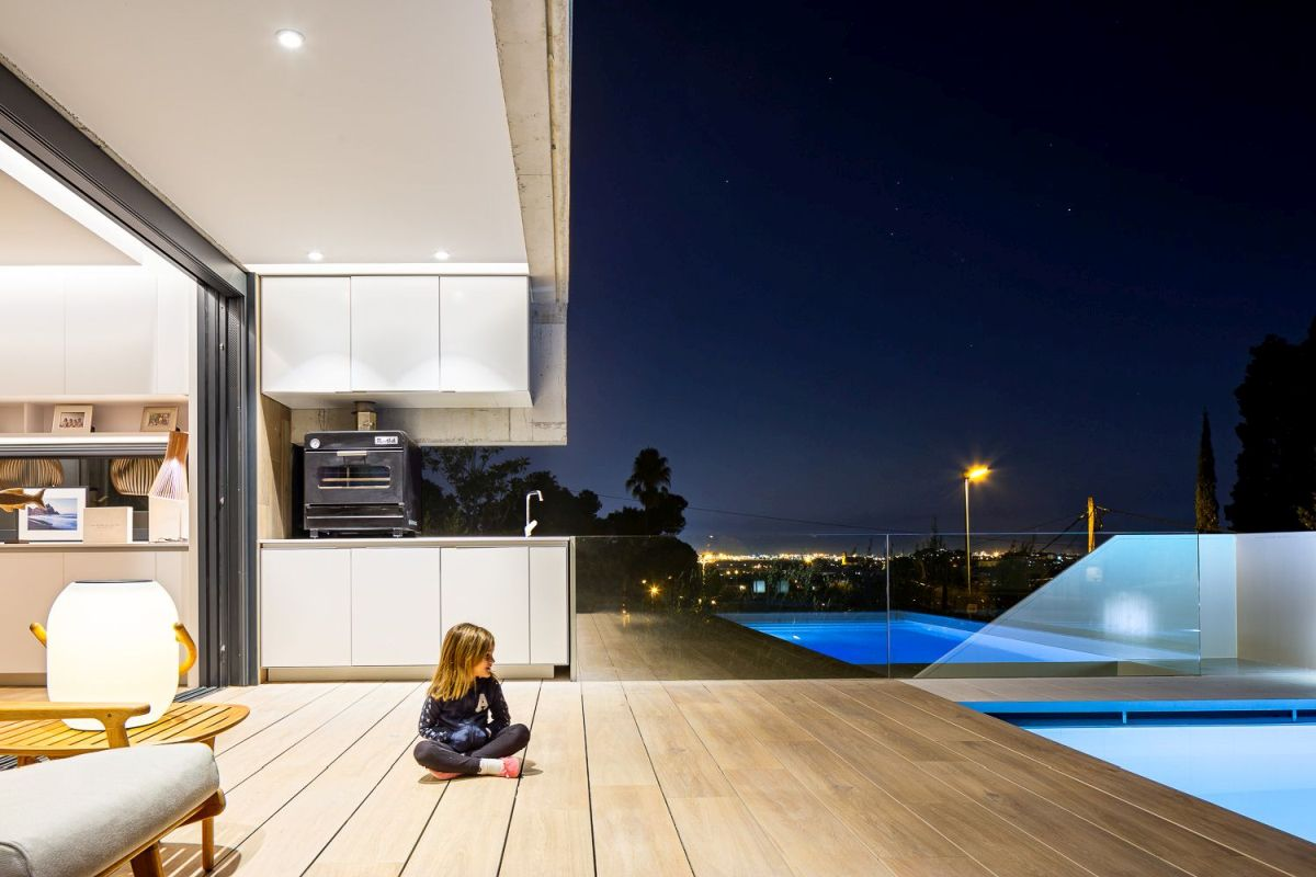 The poolside deck serves as an extension of the indoor leisure spaces, including the kitchen