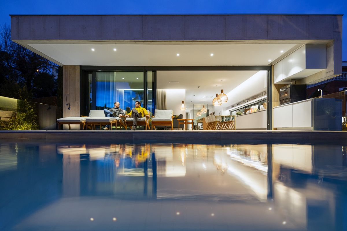The indoor and the outdoor spaces are separated by large sliding glass doors which blur the boundaries between them
