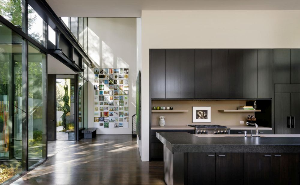 The kitchen has black cabinetry and a matching island, contrasting with the white walls that surround it