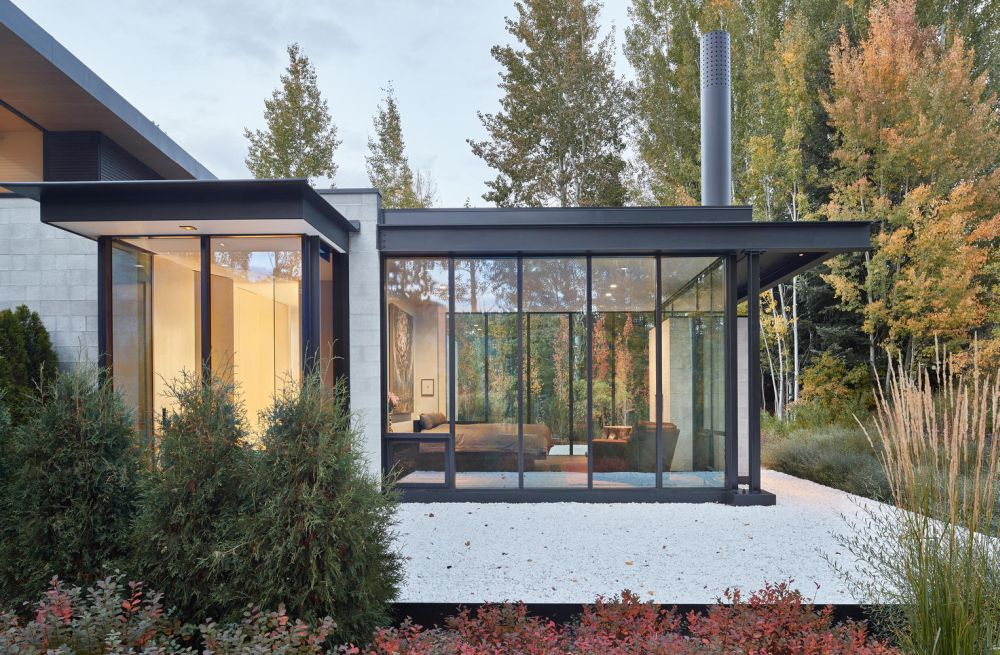 The T-shaped floor plan forms a series of glazed living spaces which take advantage of the location