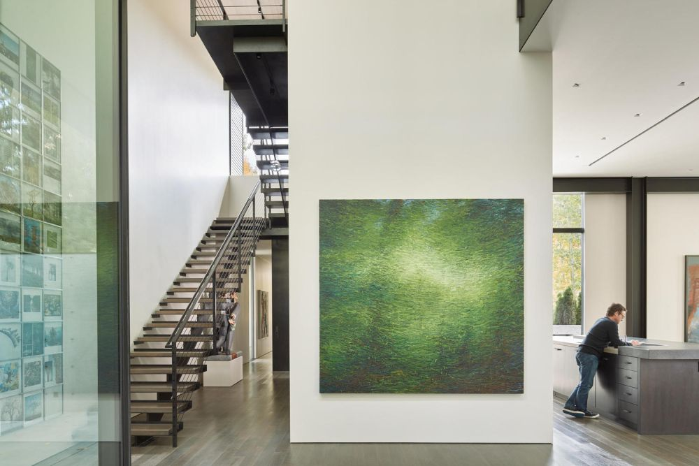 The double-height entry vestibule has a gallery next to the staircase that leads upstairs