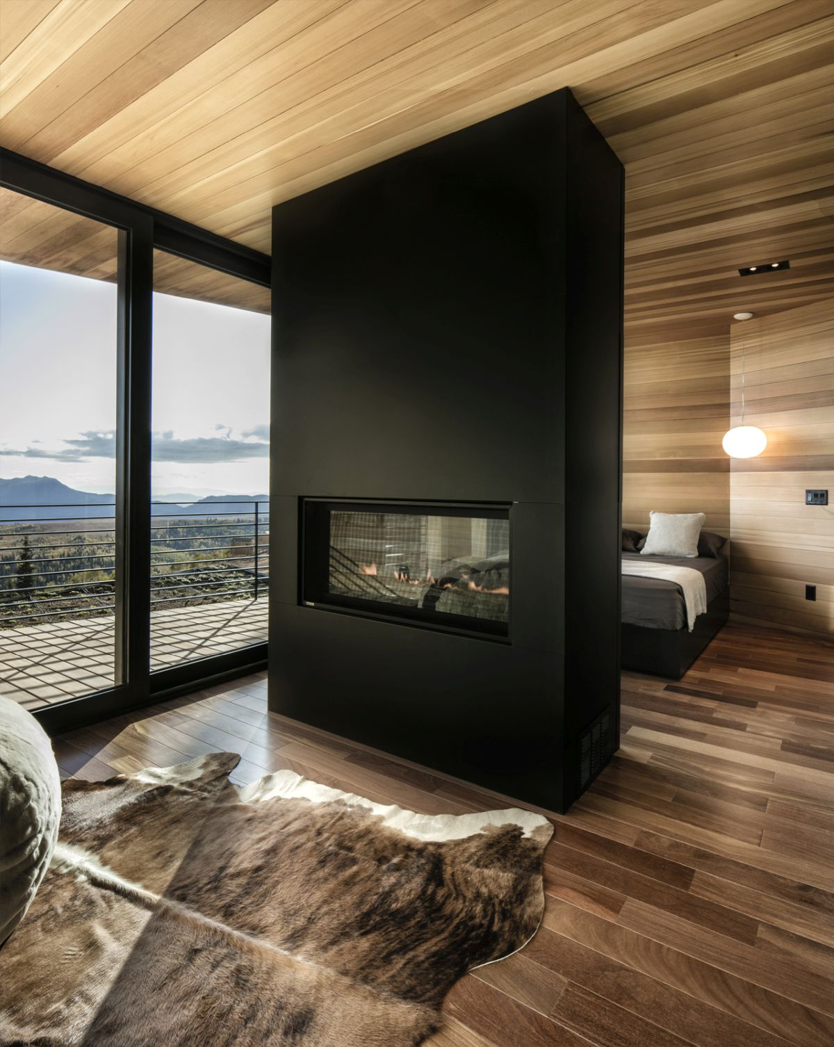 A fireplace wall divider gives the bedroom a sophisticated vibe