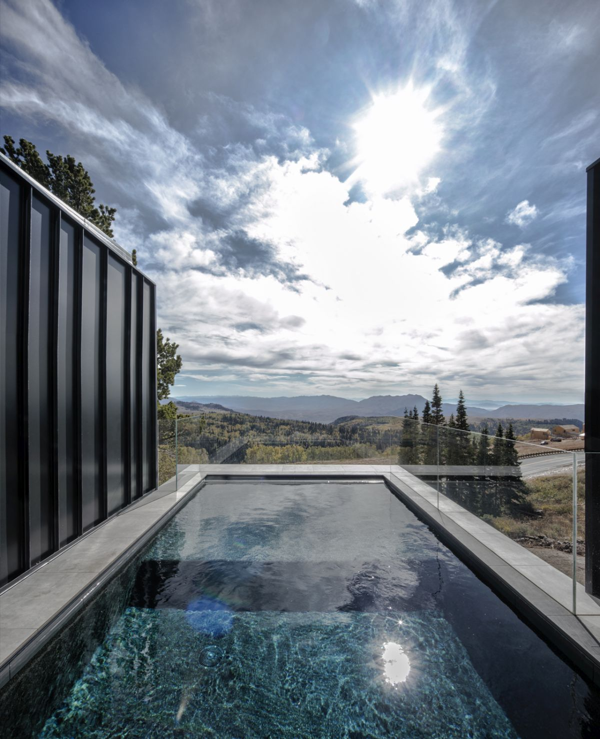 The pool is framed by transparent railings which expose it to the panoramic view