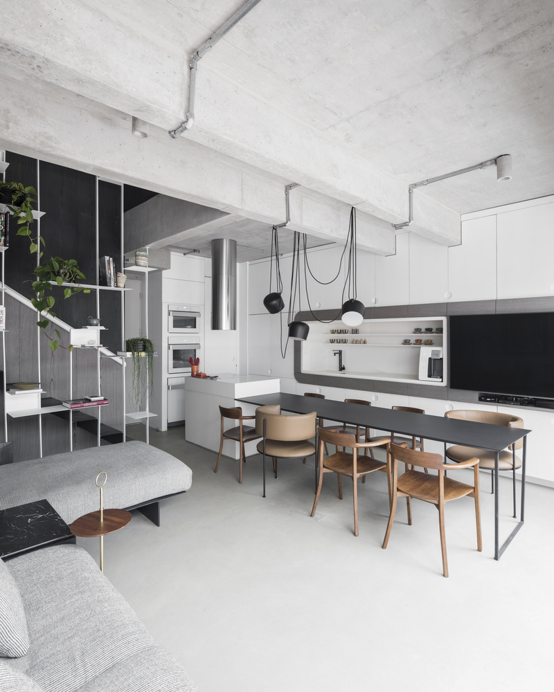 The simplicity of the concrete ceiling is punctuated by a series of sleek light fixtures
