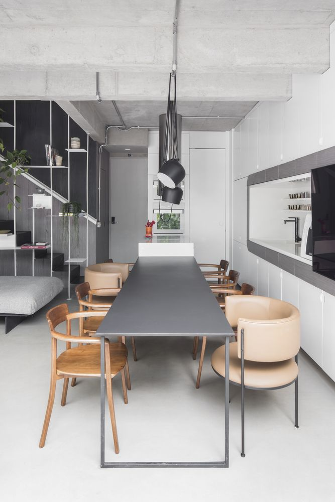 The dining table acts as an extension of the kitchen island and is complemented by different types of chairs