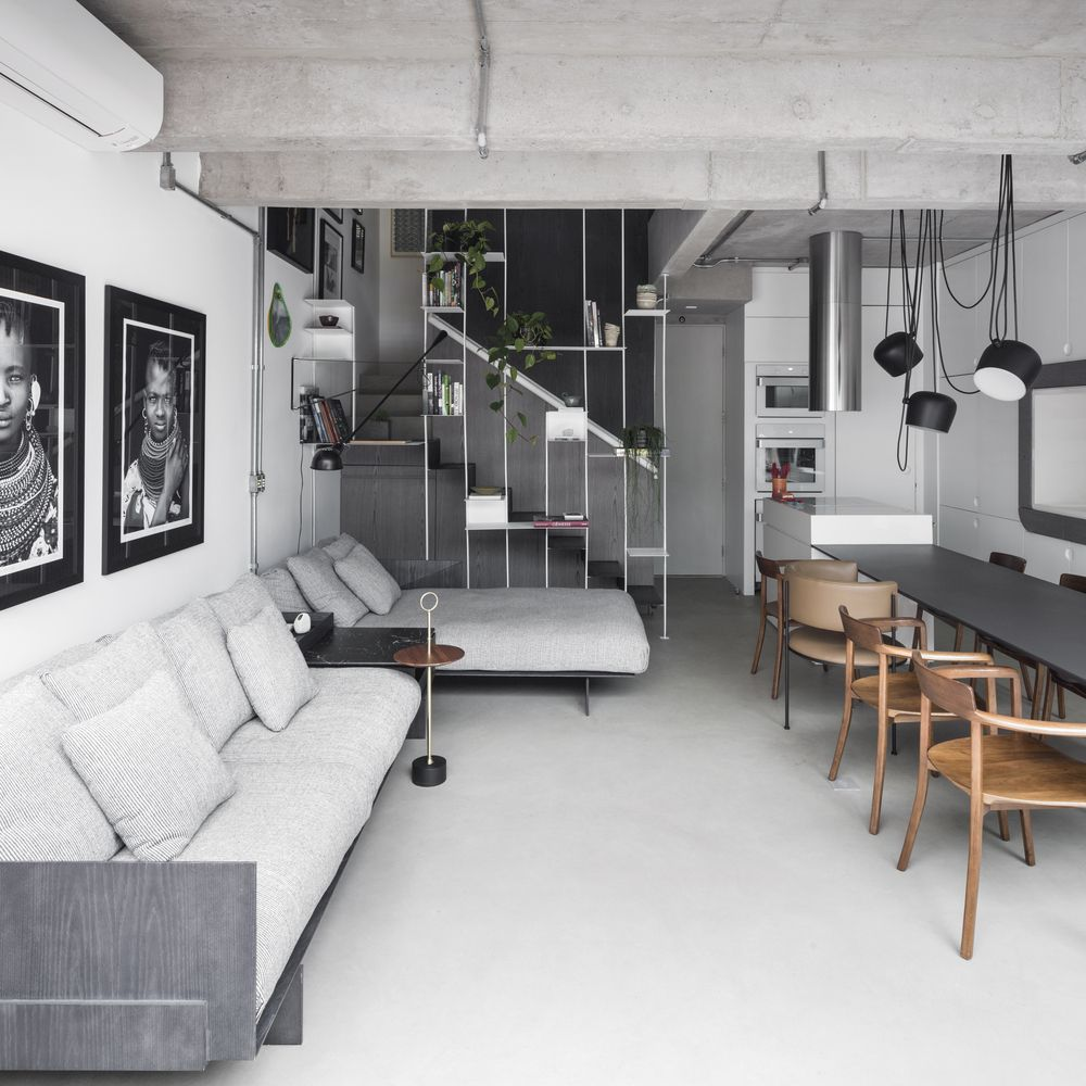 The living room sectional faces the dining table but also the TV wall placed behind