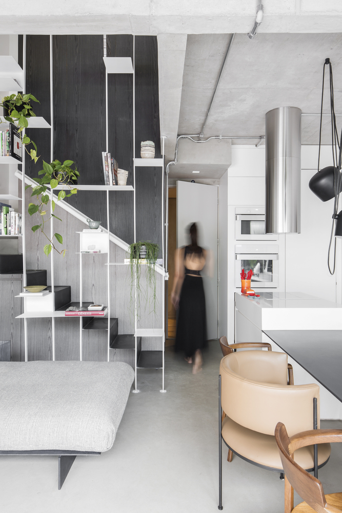 A simple staircase hidden behind a sleek metal bookcase connects the two floors