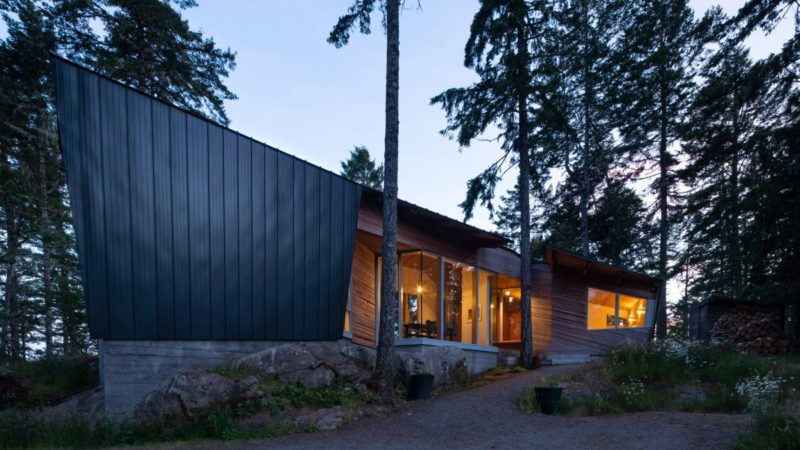 An Angular Black House Peek Between The Trees Towards The Sea