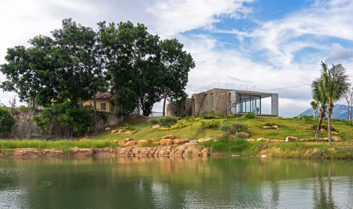 The house is situated on a small sloping hill, surrounded by large rocks and mango trees