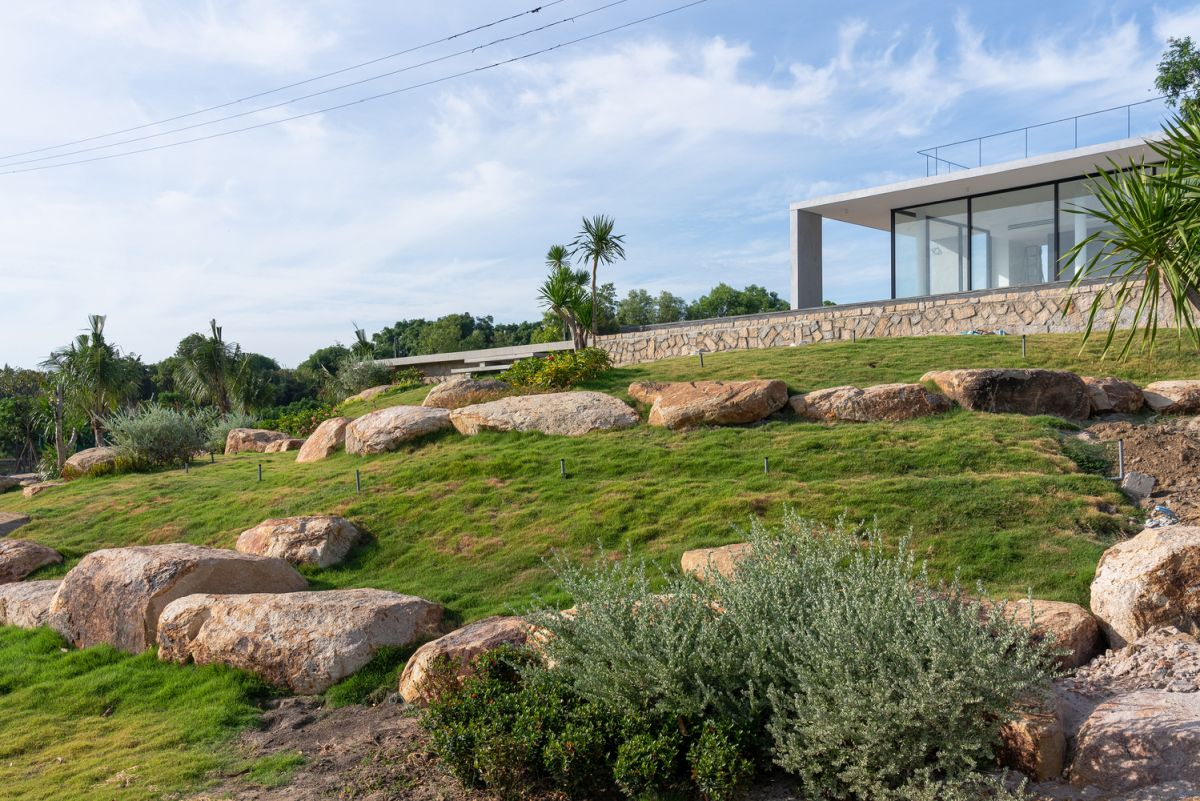 The area surrounding the house is covered by greenery with various rock structures scattered across