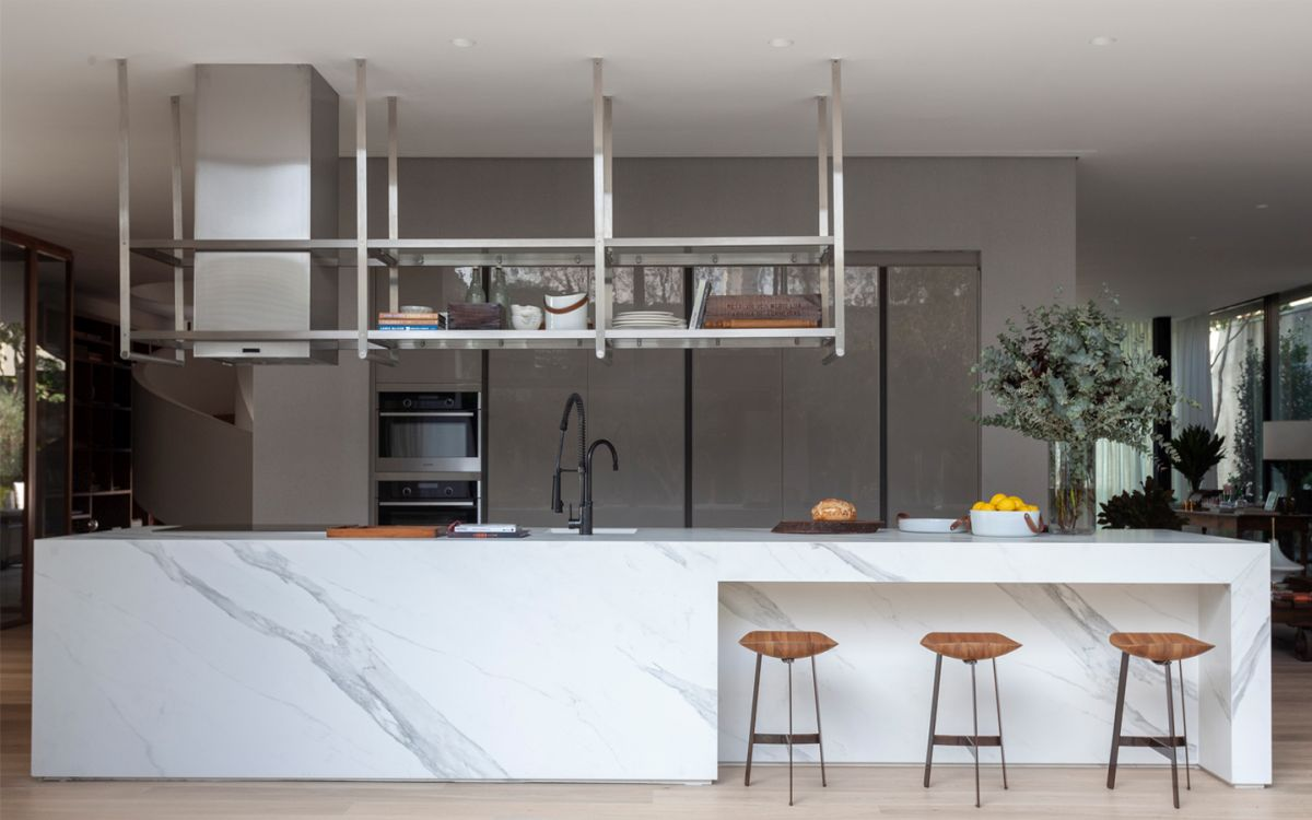 The open plan kitchen has a large white marble island which doubles as a divider