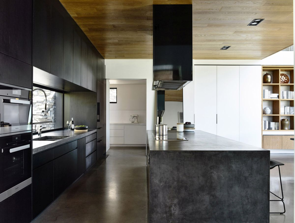 The kitchen is almost entirely black which allows it to contrast with its white surroundings