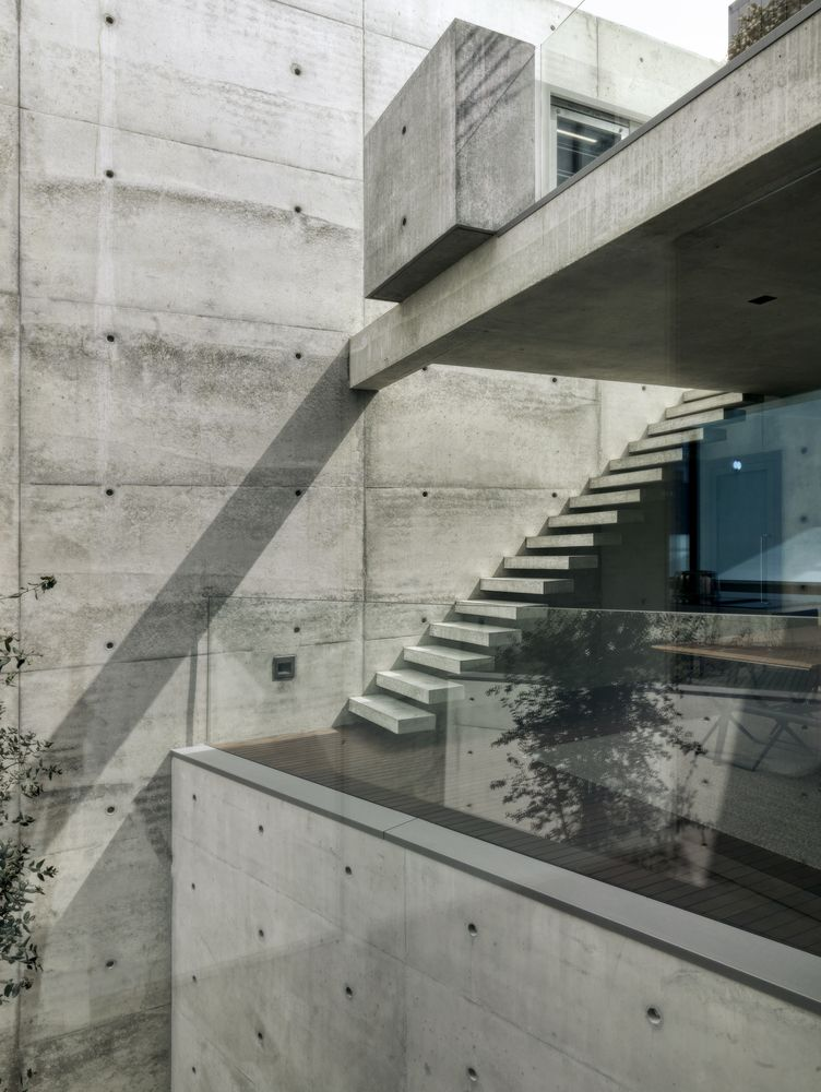 The staircase which connects the levels is made of concrete which allows it to blend into the wall
