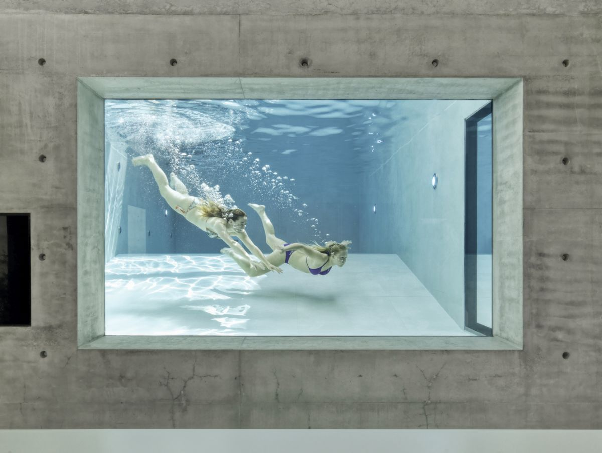 The swimming pool can be seen from the living room which makes it look like a large aquarium