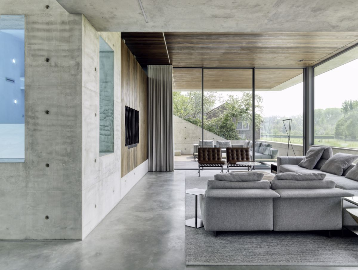 The interior design is simple and modern, including polished concrete floors, lots of exposed concrete and large windows