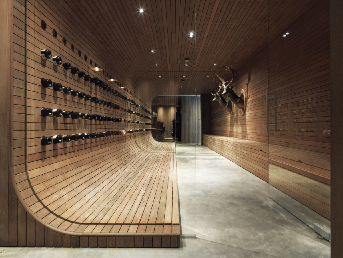 The wine cellar is very rich in wood and features a curved wall design which looks amazing