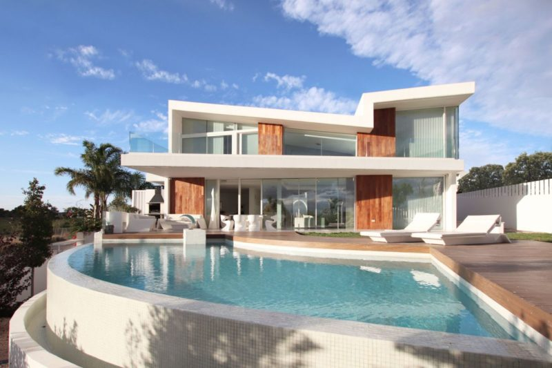 White Concrete House With A Curved Swimming Pool