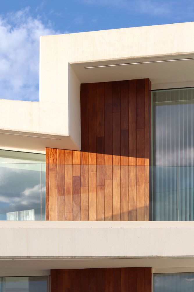 Wooden accents are strategically spread across the facade and break the overall simplicity of the design
