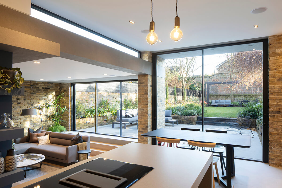 Full-height windows and glass doors bring in lots of natural light and expose the living area to the garden