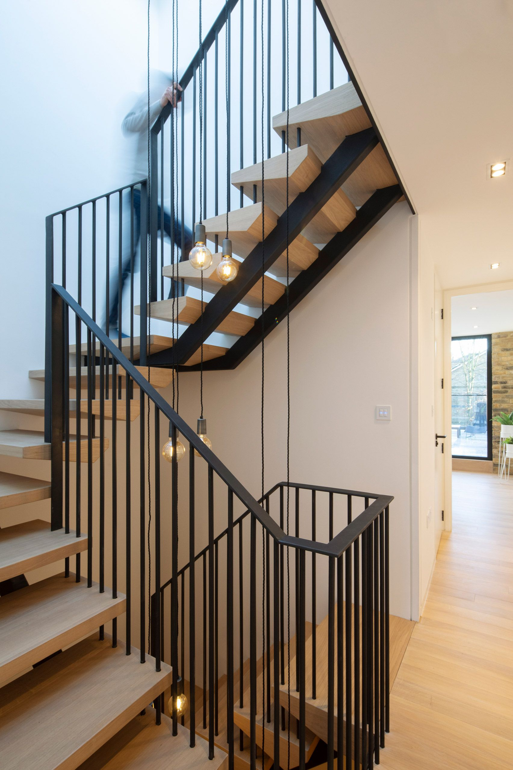 The three floors are connected through a staircase that forms a light well at the center of the house
