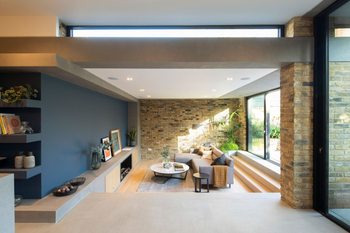 The sunken living room is positioned lower than the rest of the spaces which helps it stand out and give it a very cozy feel