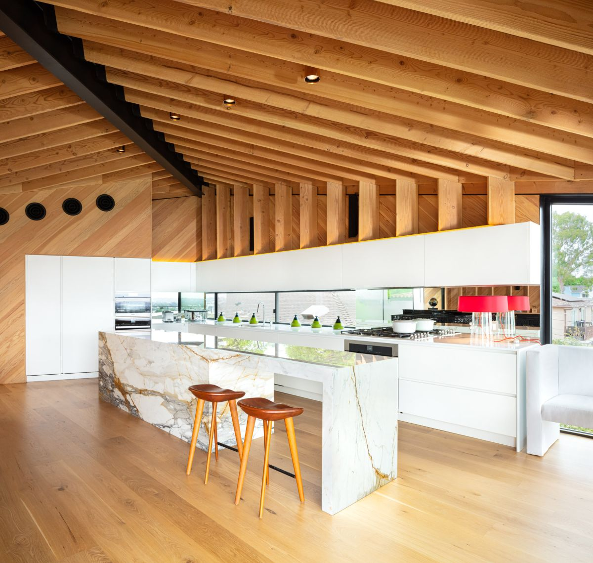 The kitchen is placed along one of the walls and has a gorgeous island made of veined stone
