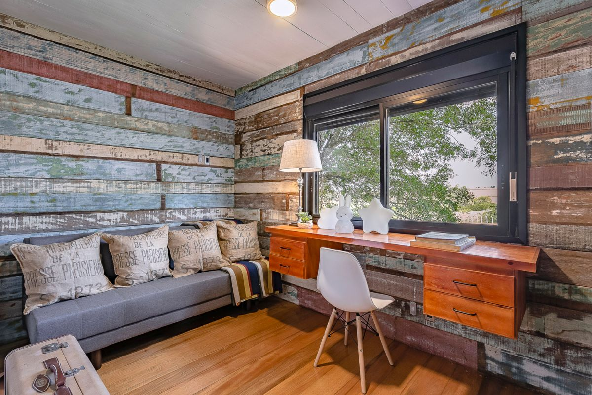 This desk area has walls covered in lots of different reclaimed board with various colors and finishes