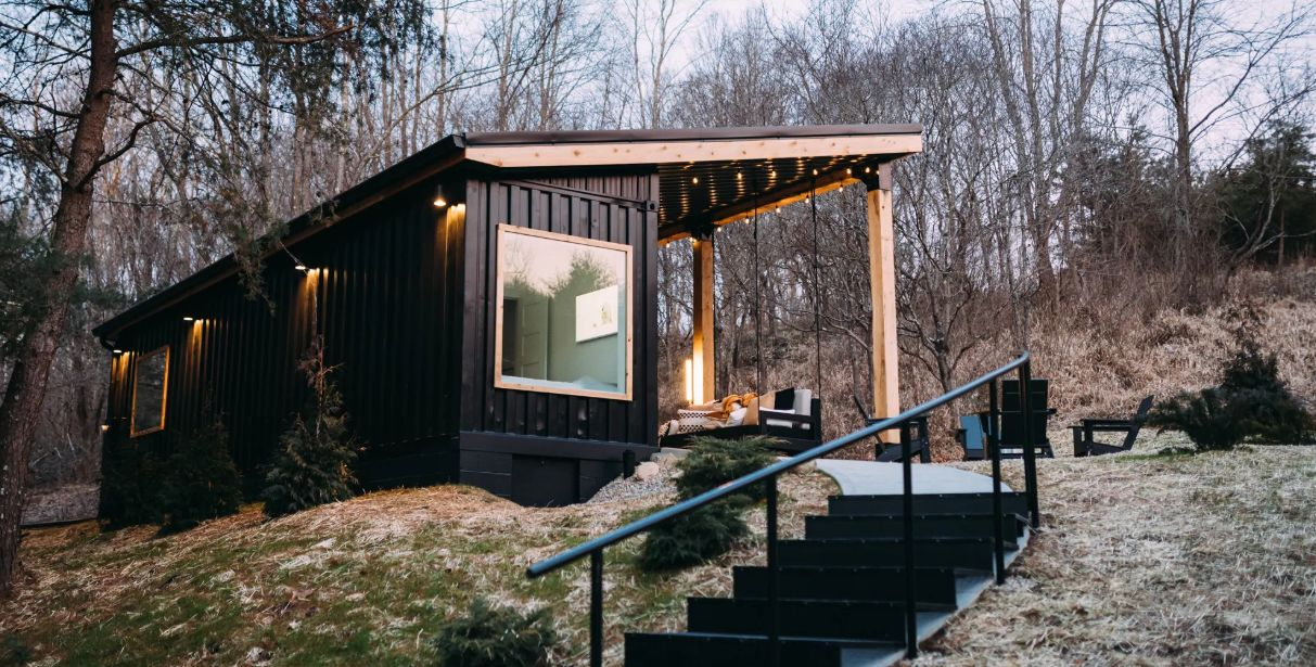 The container cabin is nestled among a wooden area with challenging topography