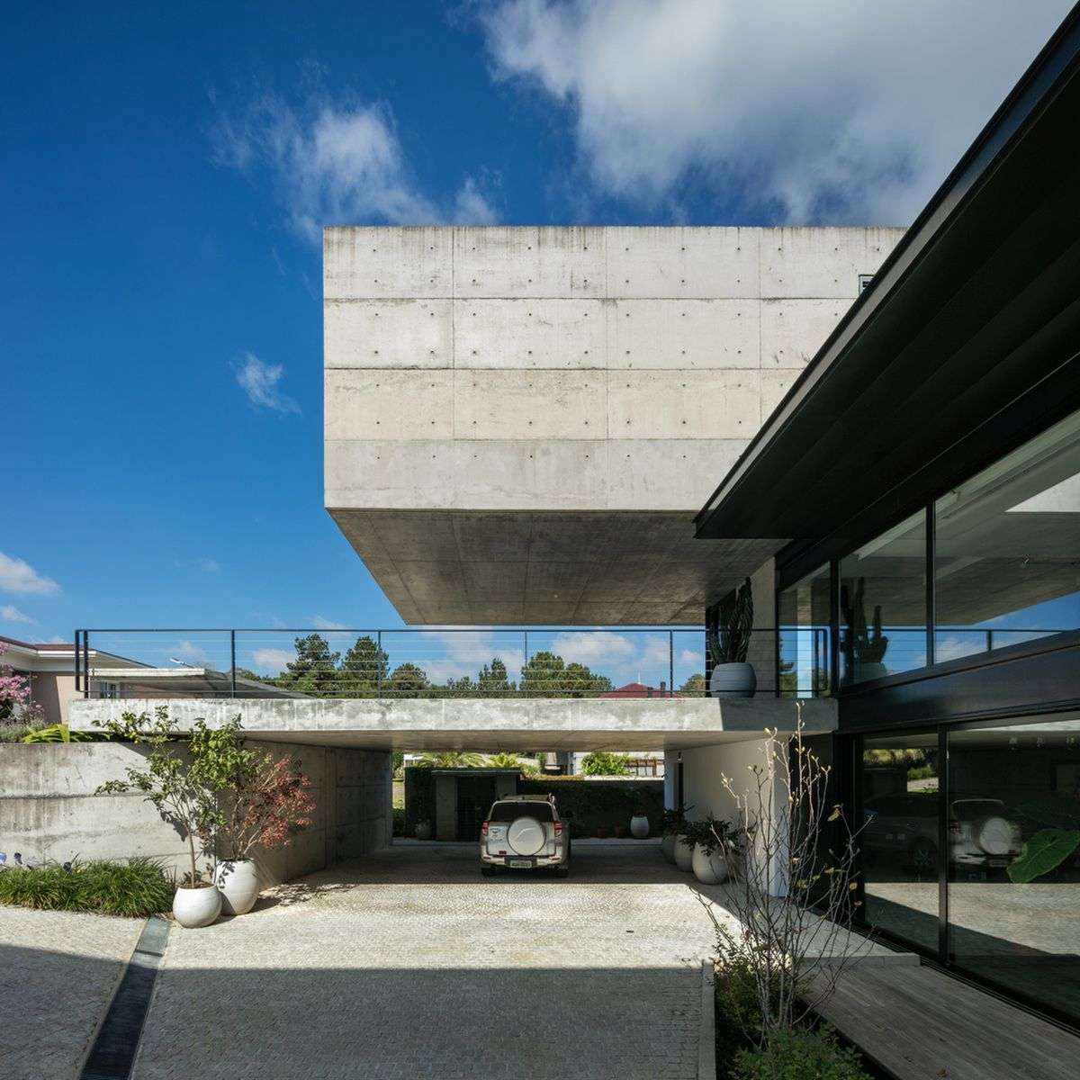 The top floor is an elongated concrete box that cantilevers above the garage and the terrace