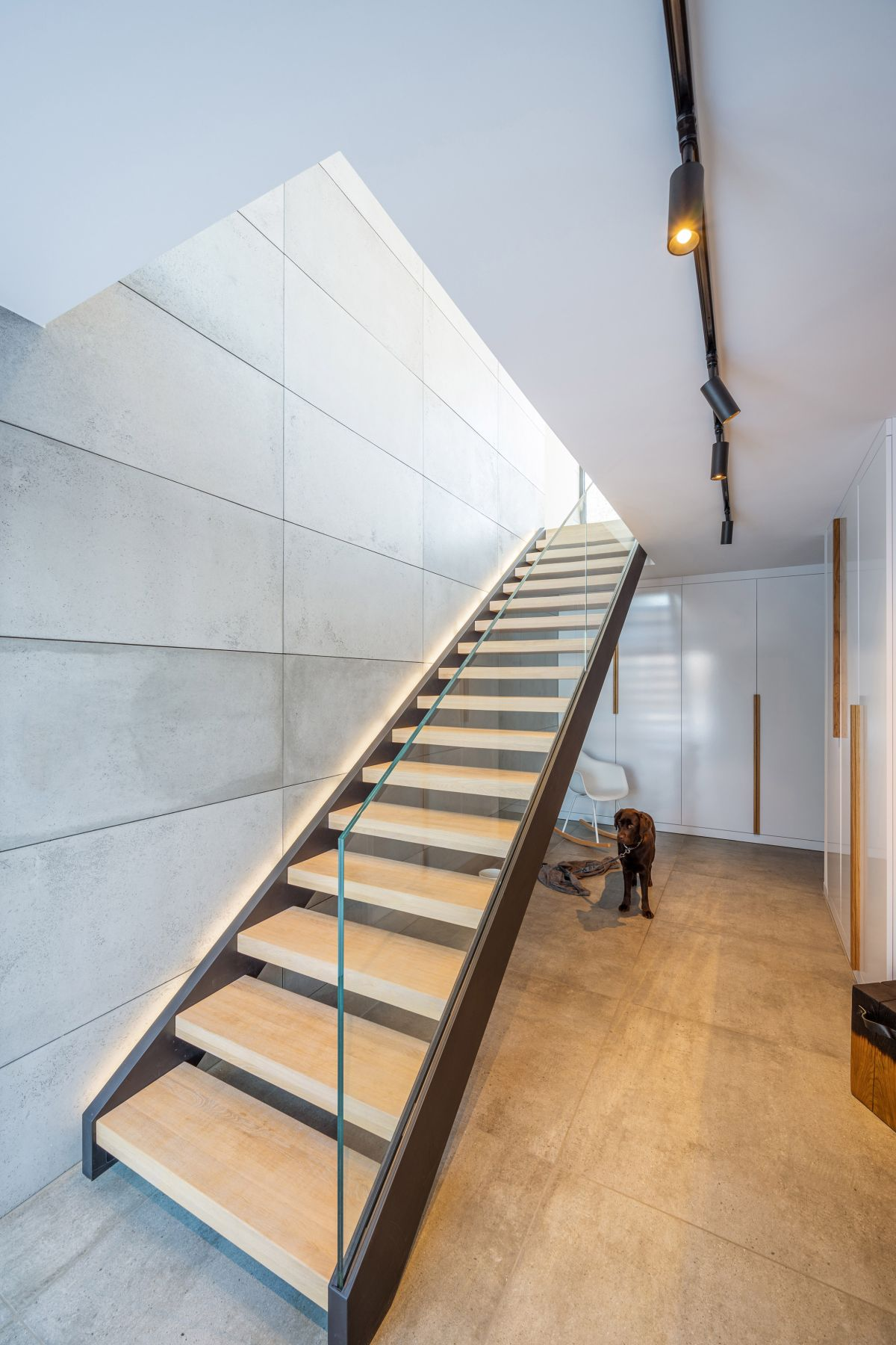 The two floors are connected by a simple staircase with transparent glass railings