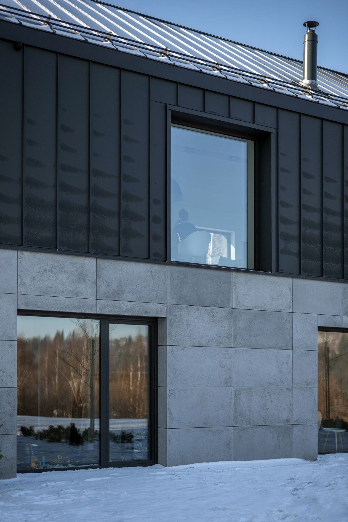 The black metal-clad section sits on top of a concrete-clad base
